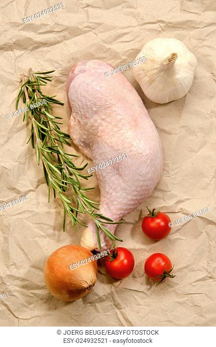 raw chicken drumstick with tomato, onion, garlic and rosemary