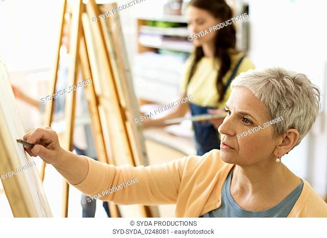 senior woman drawing on easel at art school studio