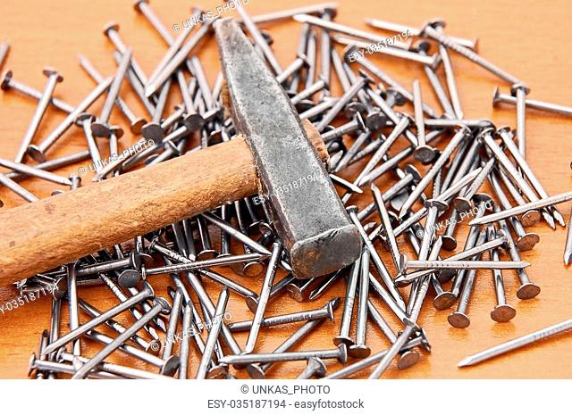 Hammer and nail on brown wooden background