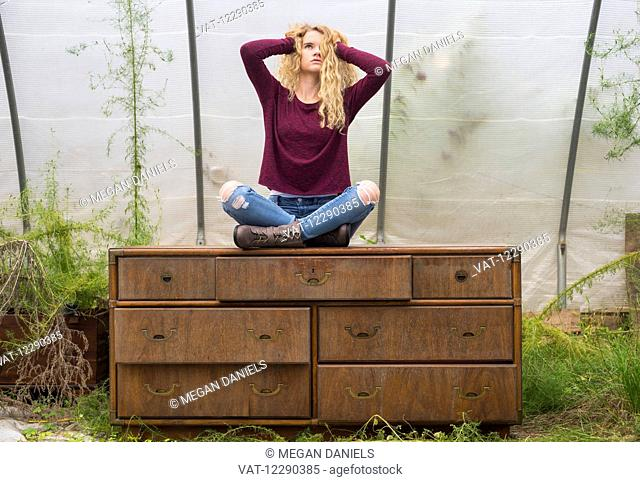 Portrait of a caucasian teenage girl with long blond, curly hair sitting cross-legged on a weathered dresser inside a greenhouse; Apex, North Carolina