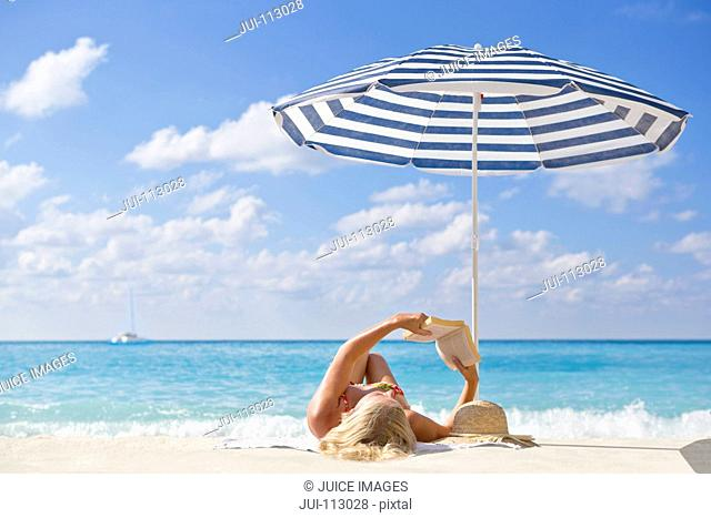 Woman laying and reading book on sunny beach under striped beach umbrella