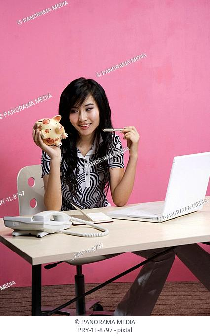 Young woman sitting by table and holding piggy bank, smiling