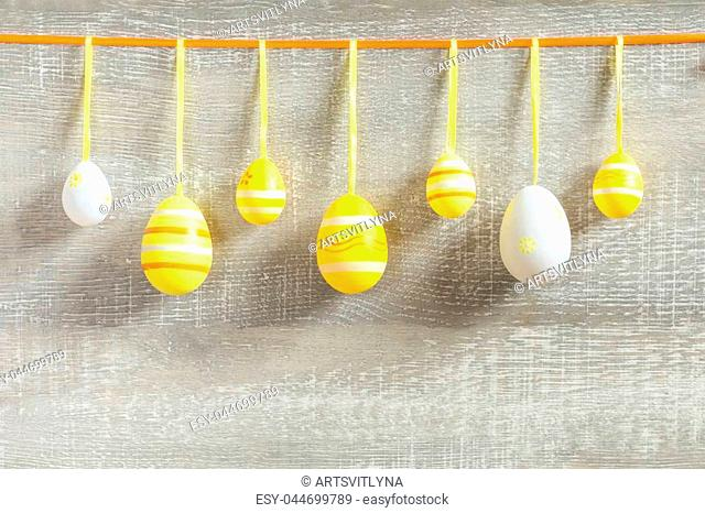Easter accessories on a light wooden surface. Yellow orange easter concept, top view, copy space, in yellow tones on a wooden surface