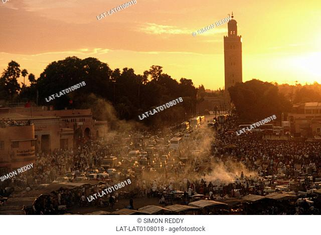 Djemaa el Fna square. Market,food centre. Night. Silhouettes. Koutoiubia mosque tower. Sunset,orange sky