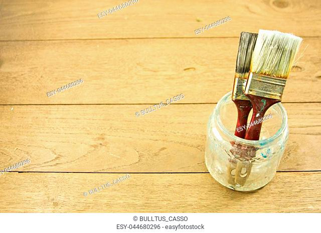 Brush for paint in glass on wooden table