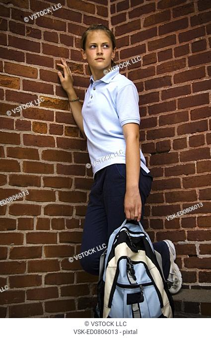 Girl in school uniform holding a backpack