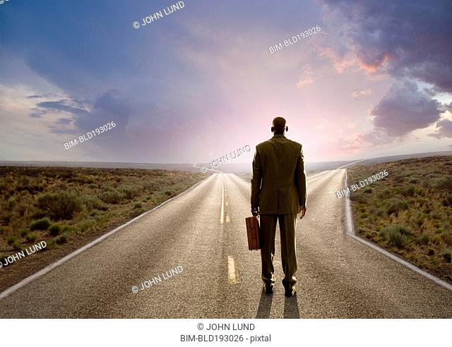 African American businessman standing at fork in road
