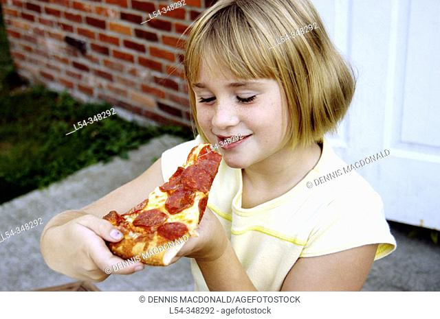 Seven year old girl eats pizza