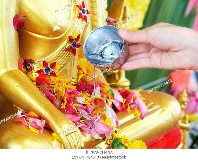 Close up hand watering to golden buddha statue on Songkran day or special buddism holidays in Thailand
