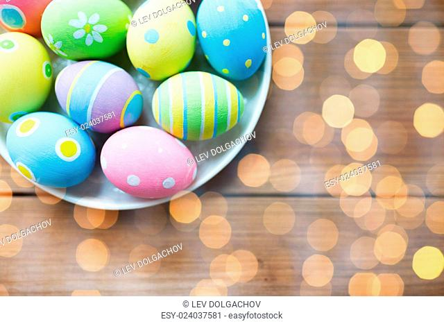 easter, holidays, tradition, advertisement and object concept - close up of colored easter eggs on plate over holidays lights