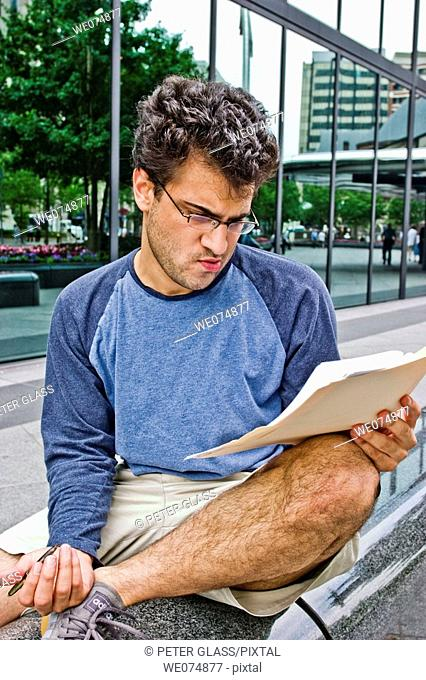 Male college student, wearing glasses, sitting outside next to a city building, studying his notes