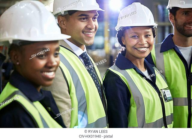 Portrait confident female worker with coworkers in distribution warehouse