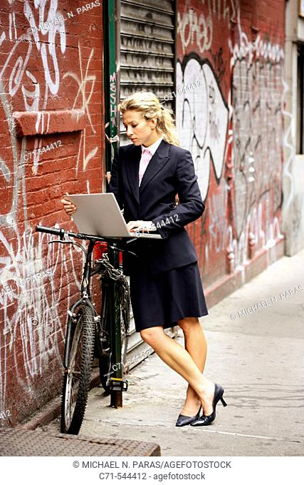 Caucassian businesswoman working on laptop leaning on bicycle against a graffiti wall