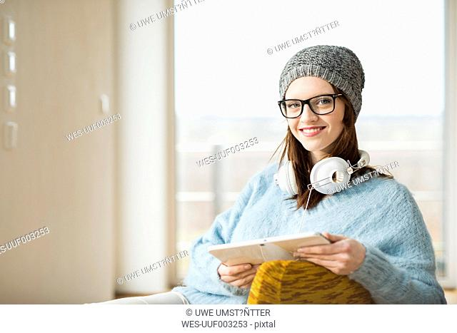 Smiling young woman with digital tablet and headphones