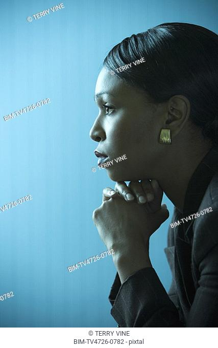 Side view of African businesswoman leaning chin on hands