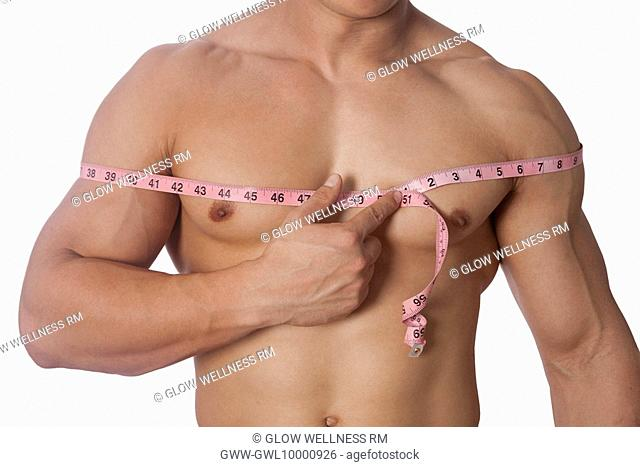 Man measuring his chest with a tape measure