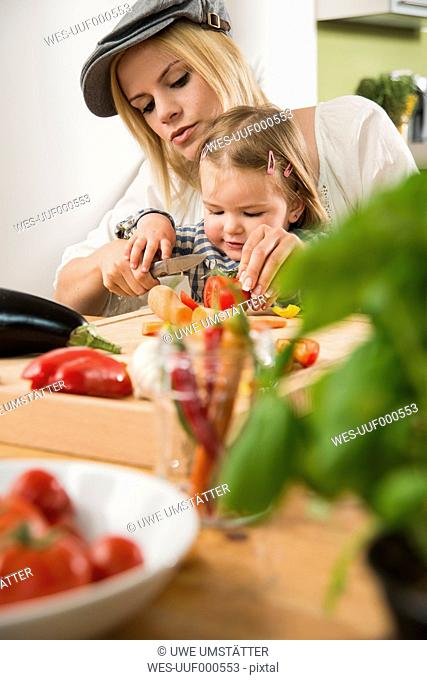 Mother and daughter cooking in kitchen at home