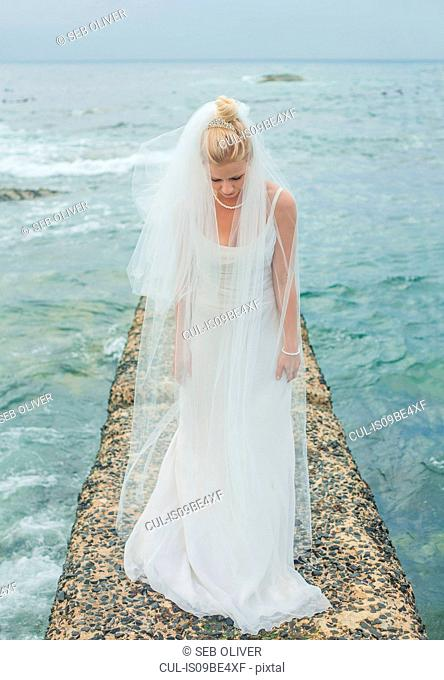 Bride bowing by sea