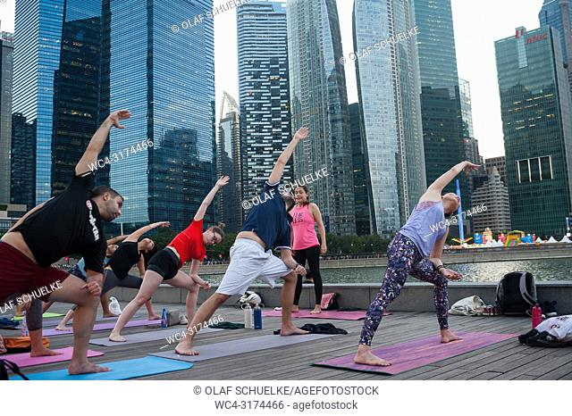 21. 12. 2017, Singapore, Republic of Singapore, Asia - Participants of a yoga class are seen doing their yoga practise in Marina Bay with the skyline of...