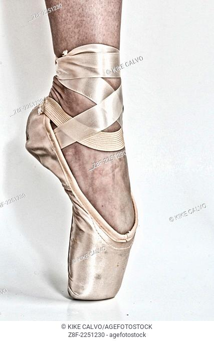 Legs of a ballerina with a black high heel shoe in one feet and a pointe ballet shoe in the other