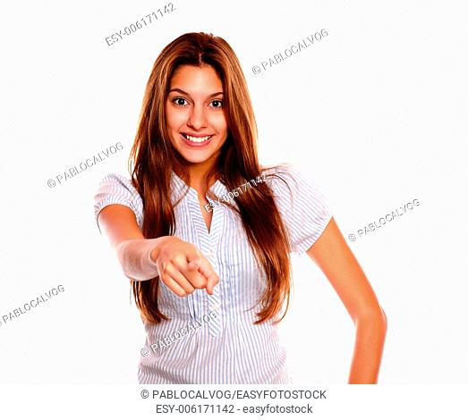Portrait of a smiling young woman with long brown hair looking and pointing at you against white background