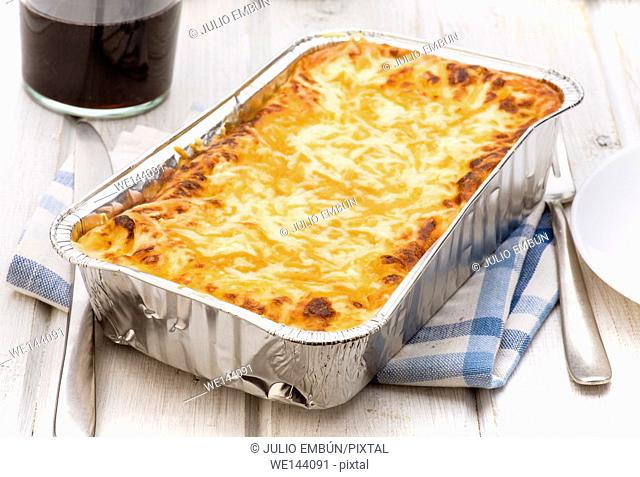 aluminum tray with cooked lasagna on wooden table