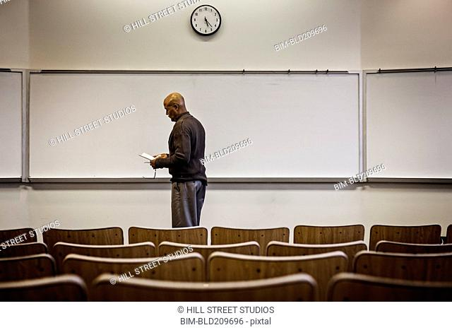 Professor standing in empty lecture hall