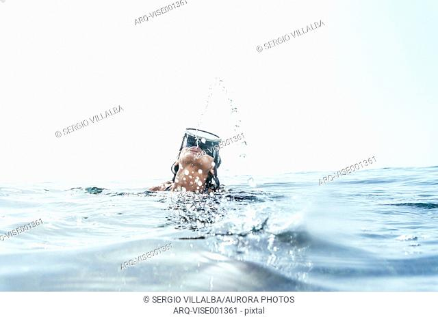 Woman in swimsuit and diving goggles emerging from waves Tenerife, Canary Islands, Spain
