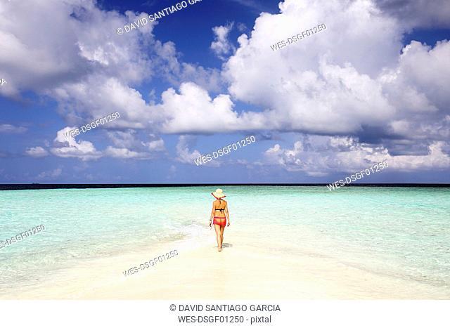 Maldives, Gulhi, woman walking on sandbank in shallow water