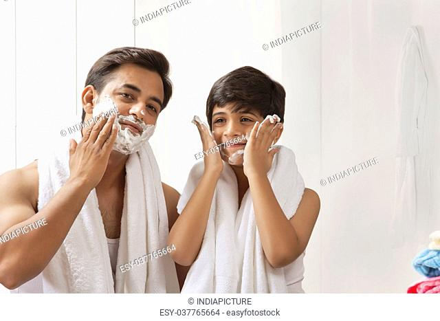 Father and son putting shaving cream on face