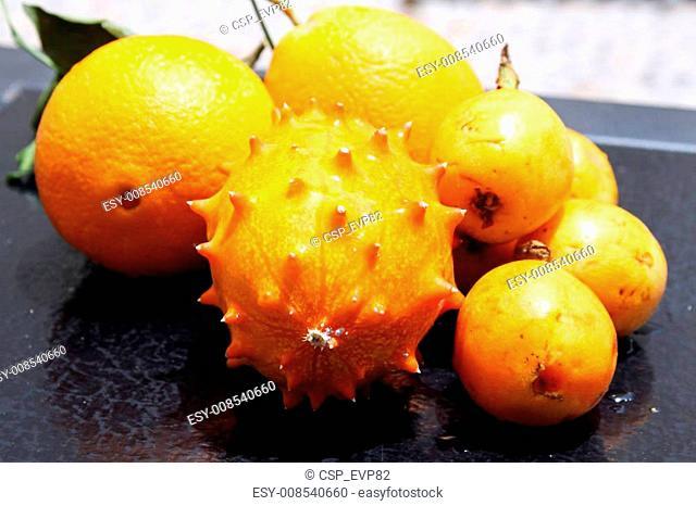Exotic fruits: orange, kiwano and loquat