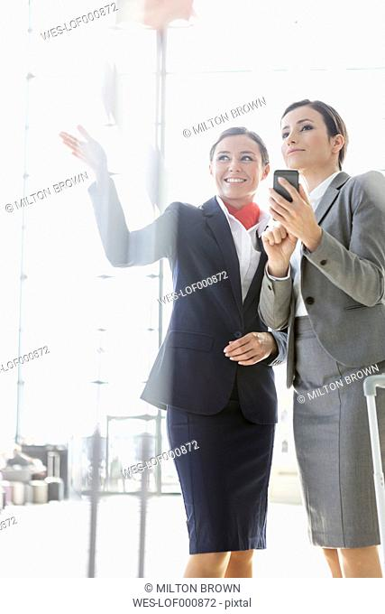 Flight attendant assisting passenger at the airport
