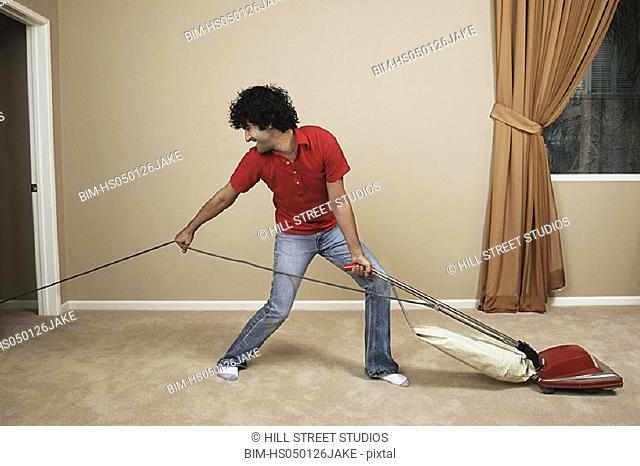 Young man pulling vacuum cord while vacuuming