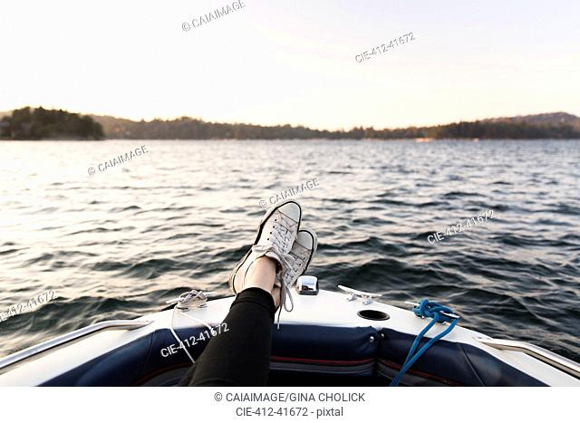 Personal perspective woman boating with feet up on tranquil lake