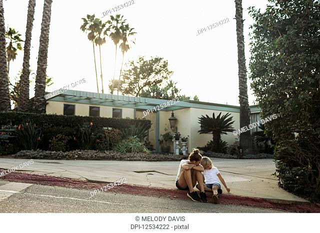 Two young girls sit on a street curb outside a house; Los Angeles, California, United States of America