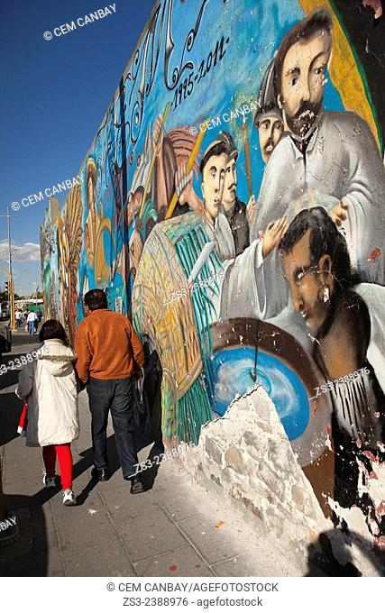People walking in the street in front of a painted wall at the town center, Puebla, Puebla State, Mexico, Central America
