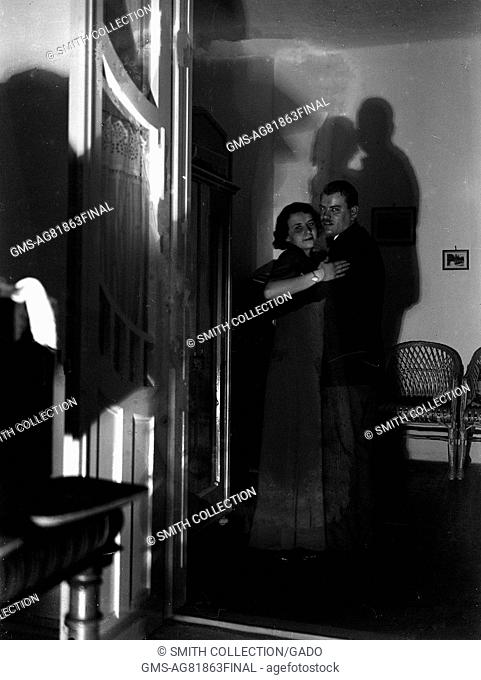 In a dark, starkly lit room, a couple dances in the middle distance, with their shadows cast on the wall behind them, Hungary, 1929