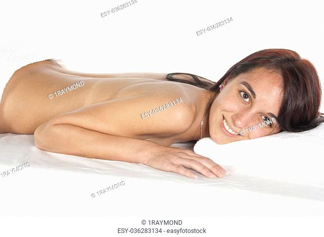 Smiling eyes open. Spa therapy pretty young brunette woman, partial nude laying on covered table. In studio on white background