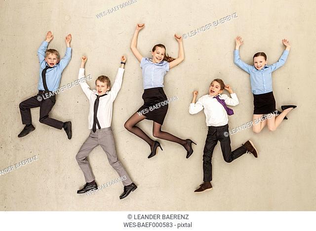 Germany, Berlin, Business kids flying against beige background