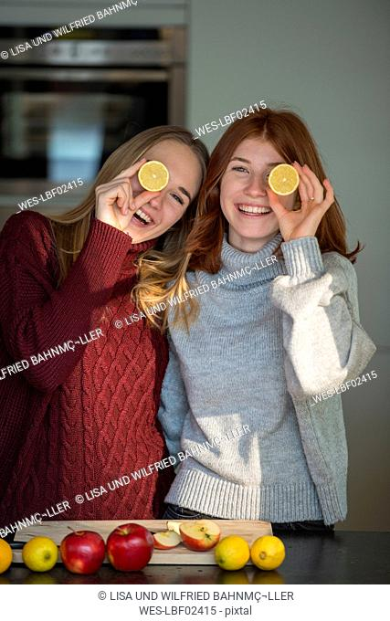 Two laughing friends holding lemon halves in front of their eyes