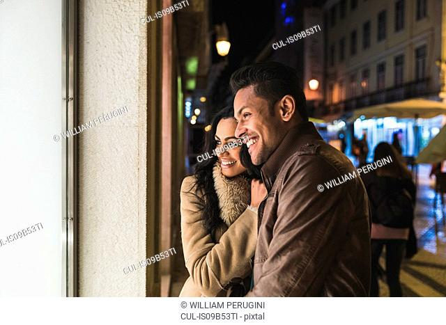 Couple looking in shop window, at night, Lisbon, Portugal