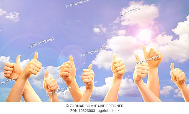 Thumbs and hands up in front of sky with sunshine