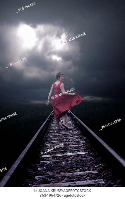 a girl in a red dress is running on railway tracks
