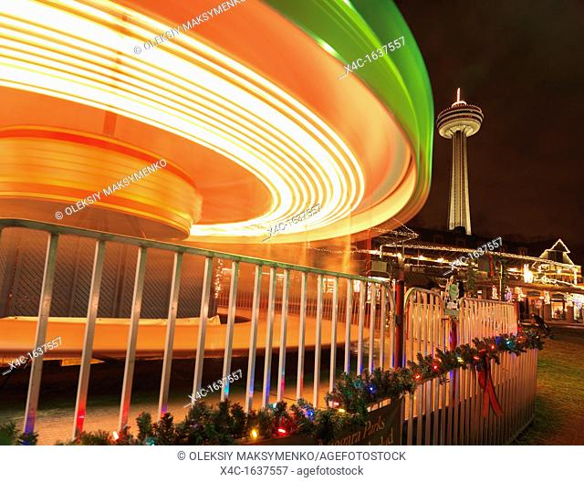 Spinning merry-go-round carousel during Christmas season at Niagara Falls with Skylon tower in the background  2011 Ontario, Canada