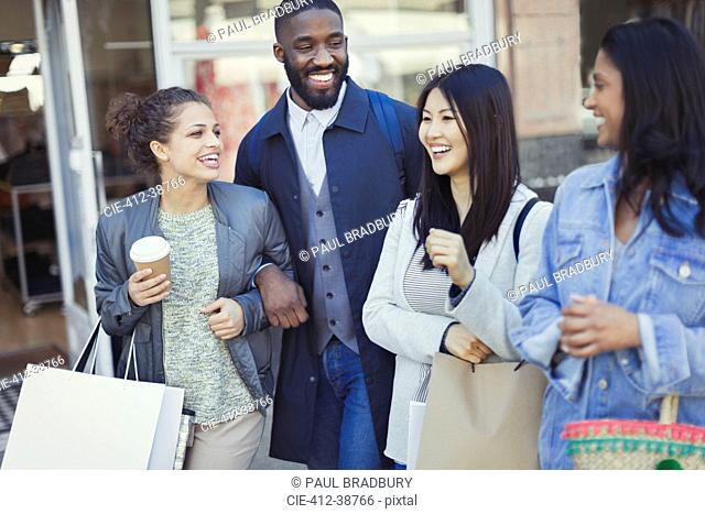 Smiling friends with coffee and shopping bags