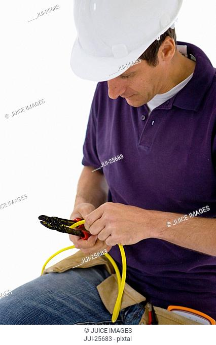Electrician with pliers stripping wire