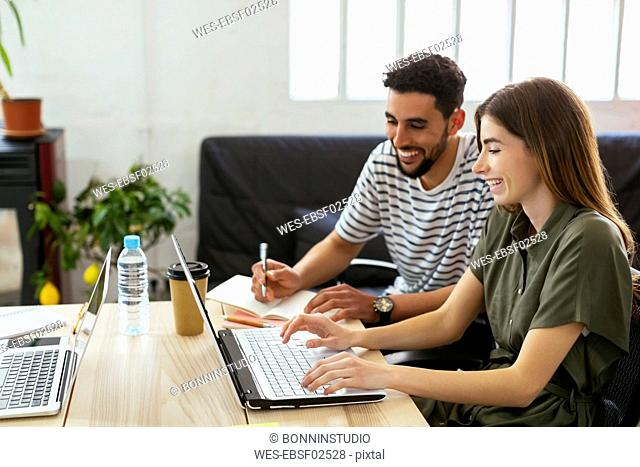 Smiling colleagues working together at desk in office sharing laptop