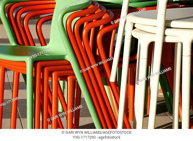 close up detail of colourful stacked plastic chairs and tables outdoors