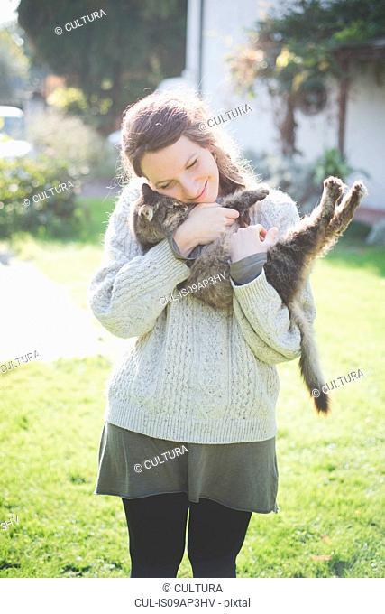 Young woman hugging cat