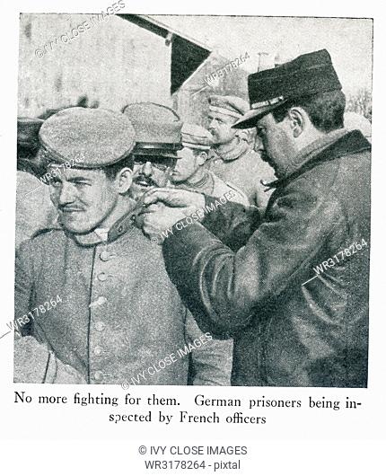 This photo dates to World War I and shows German prisoners. The caption says: No more fighting for them. German prisoners being inspected by French officers